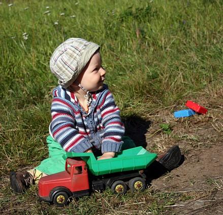 Taito mökin pihassa leikkimässä äidiltä perityllä kuorma-autolla.